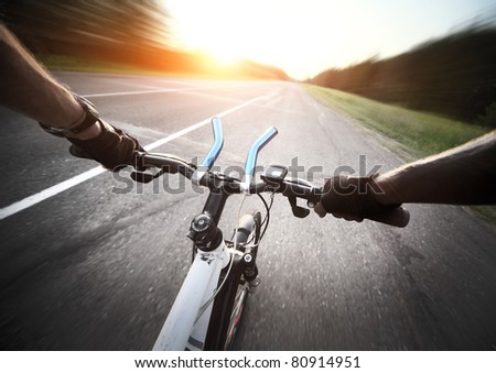 Rider's hands in gloves on a bicycle handlebar. Motion blurred #80914951