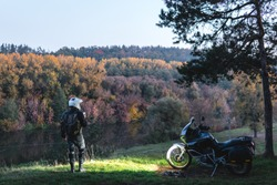 Rider standing with adventure motorcycle, Motorcyclist, A motorbike driver looks, headlights on, night forest, nature landscape. enduro travel road trip. Evening, autumn. Tourist traveler. copy space