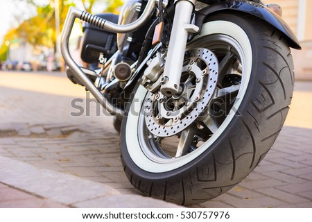 Riders will love. Cropped shot of the shot of the motorcycle forks, tire and front wheel. Disk brake system on a motorcycle. Freedom and travel concept. motorcycle parked on a street. #530757976