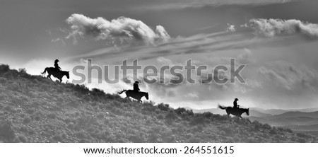Ridge Riders in Black and White - silhouettes of Cowboys and Horses riding down a ridge.  Dramatic clouds above them and range below them.