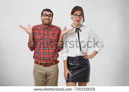 Ridiculous man and woman dressed formally, wear spectacles, shrug shoulders in bewilderment, don`t know answer on important question. Funny man has hesitations, model against white background
