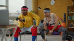 Ridiculous weird couple of fitness beginners doing arm exercises on biceps with dumbbels in wrong funny way. Parody. Humor in sports. Fake sportsmen.