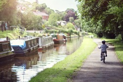 Riding a bicycle on a tow path by a canal concept for healthy lifestyle, exercising and vacations