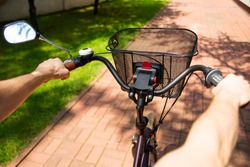 Riding a city bike on a bicycle path, pavement on a sunny day, close-up. Commuting,