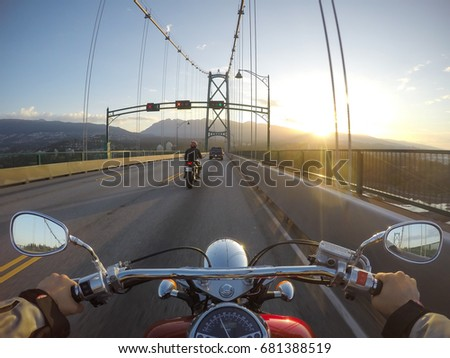 Riding a cruiser motorcycle on Lions Gate Bridge towards North Vancouver, British Columbia, Canada. Taken during a sunny summer sunrise. #681388519