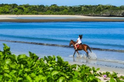 Riding a horse on the beach at the island of Fiji