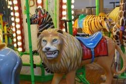 Riding around a lion, zebra, tiger, elephant carousel
