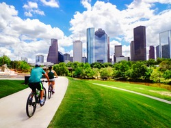 Riding Bikes on Paved Trail in Houston Park (view of river and skyline of downtown Houston) - Houston, Texas, USA