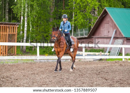 Riding lessons, teenage Caucasian girl rides a horse on outdoor manege