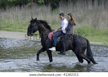 riding lovers on a black stallion in a rive