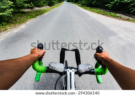 Riding on flat road asphalting in the forest. Hands on the steering wheel bicycle. Eye view from cyclist head