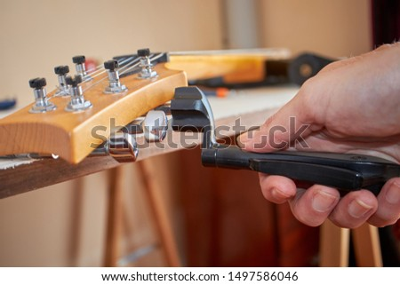 Riding strings on guitar with String Winder