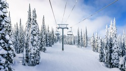 Riding the Chair Lift through the Forest of the High Alpine with Snow Covered Trees on the Hills surrounding Sun Peaks Village in the Mountains of the Shuswap Highlands of British Columbia