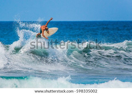 Riding the waves. Costa Rica, surfing paradise #598335002