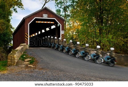 Riding Through the Covered Bridge - scooter rider moves through scene into Pennsylvania historic covered bridge
