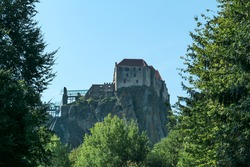 Riegersburg castle in Austria towering above the area. Dense forest overgrowing the rock. Clear blue sky above the castle. The massive fortress built on the rock. Defensive structure from middle ages