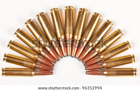 Rifle bullets packed in a half circle placed on a white surface