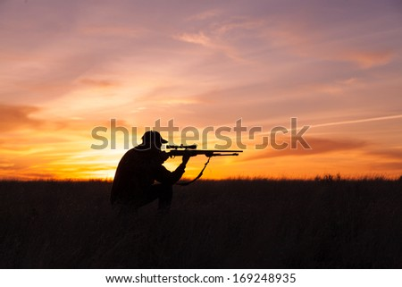 Rifle Hunter Silhouetted in Beautiful Sunset