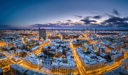 Riga city panorama in winter time. Street lights glowing. Snowy rooftops. Iconic buildings and architecture. Drone footage.