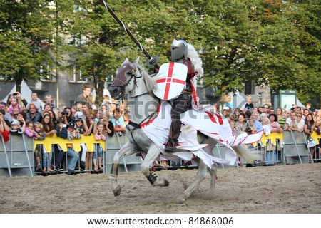 RIGA, LATVIA - AUGUST 21: Member of The Devils Horsemen stunt team riding white horse and holding spear during Riga Festival on August 21, 2011 in Riga, Latvia