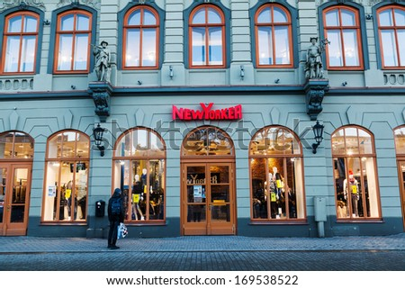 RIGA, LATVIA - DECEMBER 13, 2013: New Yorker store in an old building in the old town with unidentified man on December 13, 2013 in Riga. It is a German apparel company, 2011 existed 863 stores in Europe.