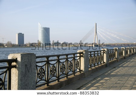 Riga, Latvia. Quay of the river Dvina and a kind on the bridge and high-rise buildings.