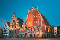 Riga, Latvia. Schwabe House And House Of The Blackheads At Town Hall Square, Ancient Historical Landmark And Popular Touristic Showplace In Summer Evening. Night Illuminations.