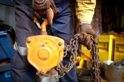 Rigger high risk worker wearing heavy duty CS5 hand protection glove, doing checking inspection a heavy duty 3 tones yellow lifting chains block prior used on construction site Perth city, Australia
