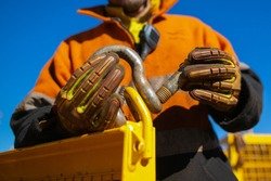 Rigger high risk worker wearing safety heavy duty glove, inserting pin into D- shape shackle which its connecting on  crane lifting lug gate hook prior lift at construction site Perth city