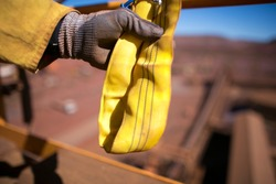 Rigger inspector high risk worker hand wearing heavy duty glove holding inspecting a yellow three lifting sling prior used in Sydney city construction building site, Australia