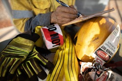 Rigger inspector high risk worker   inspecting checking yellow three lifting sling with red danger tag safety glove personal lock tags helmet prior used construction building site, Australia