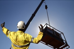 Rigger wearing a glove standing raising using a hand signal by moving finger slowly to directing communication with crane driver to move the boom up at construction site, Sydney, Australia