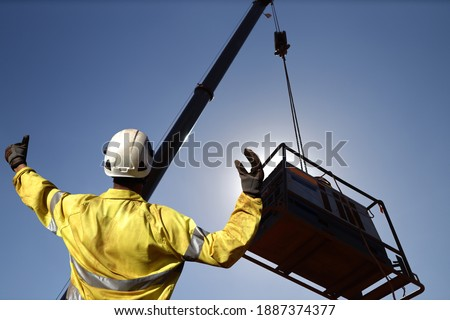 Rigger wearing a glove standing raising using a hand signal by moving finger slowly to directing communication with crane driver to move the boom up at construction site, Sydney, Australia    Foto stock ©