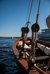 Rigging and ropes on an old sailing ship for summer sailing. Ropes on the boat. Rook, close-up overlooking the lake or sea. Sailing boat pulley, block and tackle with moored nautical rope.