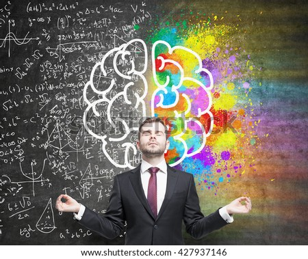 Right and left hemispheres, creative and analytical thinking concept with businessman meditating against chalkboard with sketch #427937146
