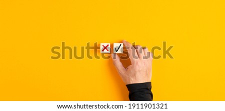 Right and wrong icons on wooden cubes with male hand choosing the right icon on yellow background. Approving, voting or right decision concept. Сток-фото ©