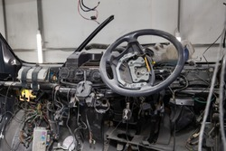 right-hand drive car interior in the back of a van with a disassembled dashboard and view on steering wheel during preparation in a vehicle repair workshop. Auto service industry