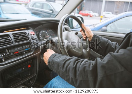 Right hand drive car. Man hand holding steering wheel #1129280975