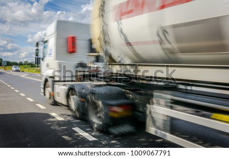 Right Hand Drive Heavy Goods Vehicle / Tanker / Truck / Lorry Whizzing By With Motion Blur On A Sunny Day With Blue Sky And White Cloud