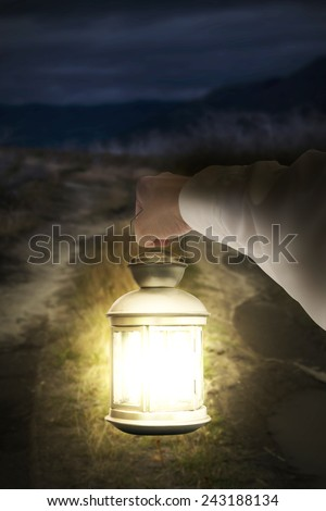 Right hand holding light illuminating dark road at night background