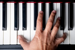 right hand playing a D octave chord on the piano