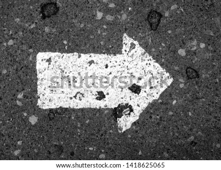 Right pointing arrow on asphalt in black and white. Signs and symbols. #1418625065