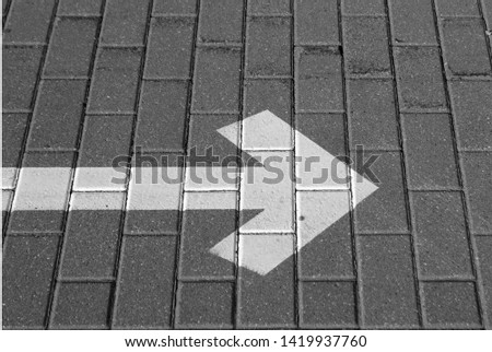 Right pointing arrow on asphalt in black and white. Signs and symbols. #1419937760