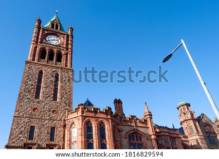 Right-side view of Guildhall in Derry/Londonderry, Northern Ireland, built in the 19th century with red bricks and the clock tower, meeting place of the local city council.