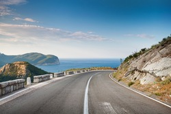 Right turn of mountain highway with blue sky and sea on a background
