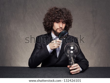 rigorous businessman examining a huge bulb carefully with a magnifying glass on grunge background