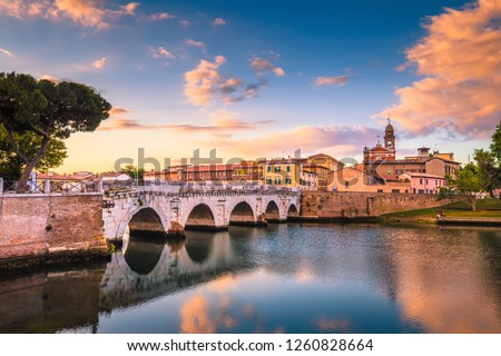 Rimini cityscape. Tiberius bridge famous sightseeing in Rimini at dawn. Summer sunrise in Rimini historic center.