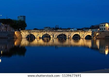 Rimini, Emilia Romagna, Italy: ancient Roman bridge of Tiberius at night after sunset with city lights, dark blue sky