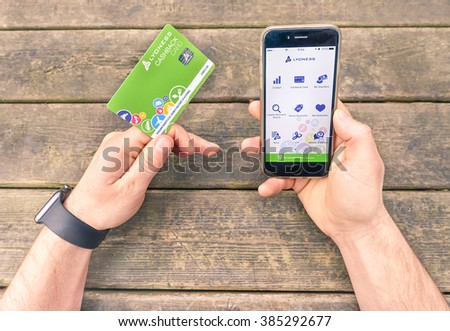 RIMINI, ITALY - FEBRUARY 26, 2016: Close up of man using Lyoness app showing on Apple Iphone 6 with wood background,Lyoness is smartphone app-based on cashback money system  #385292677