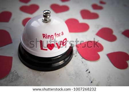 Ring bell for a love and many hearts on a wood background. #1007268232
